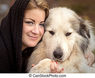 Woman cuddling a big shepherd dog