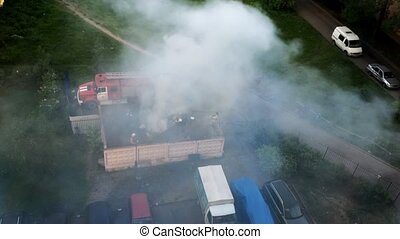 View at firefighters extinguish fire in dustbin from...