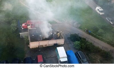 Firefighters extinguish fire, spray water on dustbin. Camera...