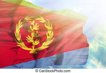 Eritrea waving flag against blue sky with sunrays