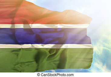 Gambia waving flag against blue sky with sunrays