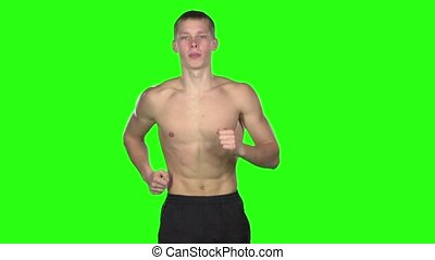 Man in a shorts running. Green screen. Slow motion