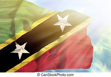 St Kitts and Nevis waving flag against blue sky with sunrays
