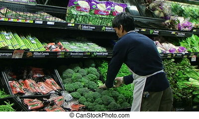 Man Facing Broccoli In Produce - Man facing broccoli in...