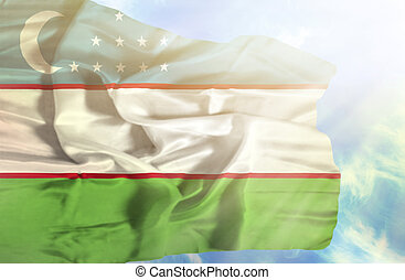 Uzbekistan waving flag against blue sky with sunrays