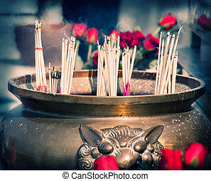 Buddhist shrine with smoking incense sticks and roses,...