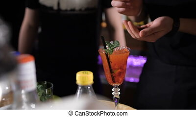 Bartender is making cocktail. Red cocktail decorated with...