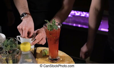 Bartender is making cocktail. complex preparation of various ingredients