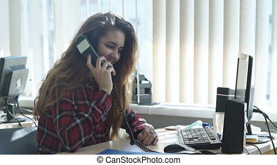 Beautiful girl sitting in office and talking on the phone -...