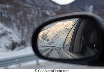Mountains snowy landscape reflected in the car rear view...