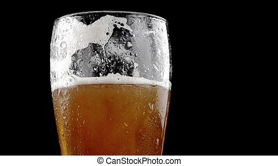 pouring fresh beer with foam into glass on black background