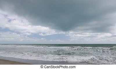 Waves and Clouds Loop - Clouds look down upon a a Florida...