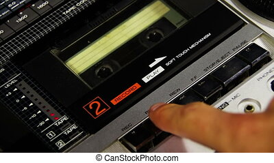 Pressing a Finger Play and Stop Button on a Tape Recorder -...