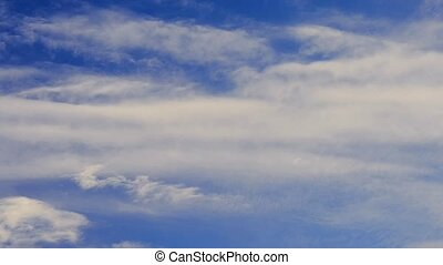 Cumulus and cirrus clouds move on background of blue sky -...