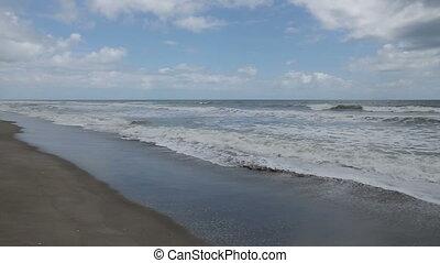 Seaside Loop - Waves break on a sandy Florida beach under a...