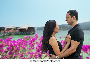 Happy interracial couple in love at sea side with bungalow...