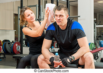 Girl with a towel care about their guy in the gym
