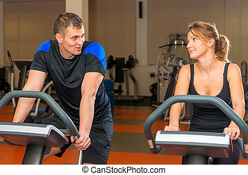 portrait of men and women on exercise bikes in the gym