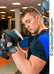 portrait of a man exercising with dumbbells in a gym