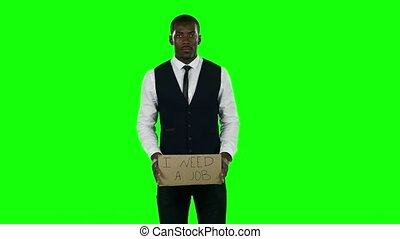 Businessman wearing a suit with a cardboard sign that asks about desire to find a job. Green screen