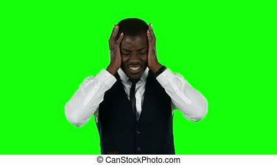 Businessman shouting the hands on his ears. Green screen