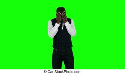 Frustrated businessman holding his head. Green screen -...
