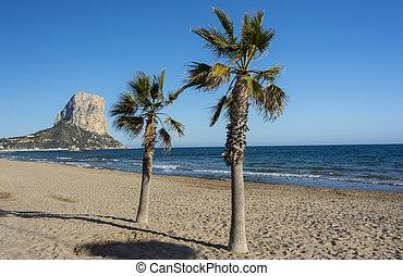 Penon de Ifach, palm trees and the Mediterranean sea in Calpe, Spain.
