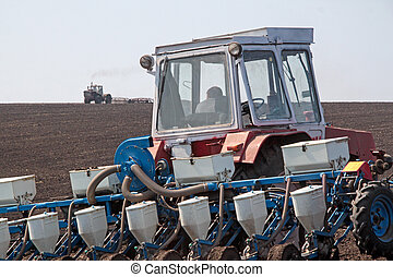 Tractor with sower on the field in bright sunny spring...