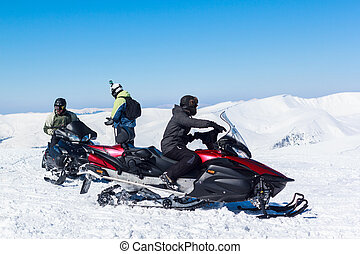 man on a snowmobile on a snow-covered mountain