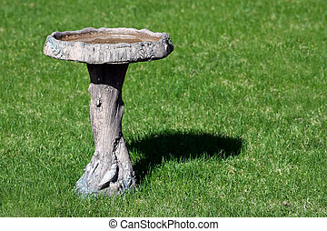 Bird Bath - A photo of a bird bath on a green lawn on a...