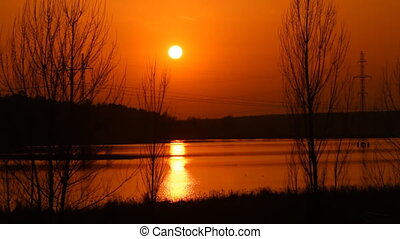 Sunset over the lake - the sun sets behind the hill on a...