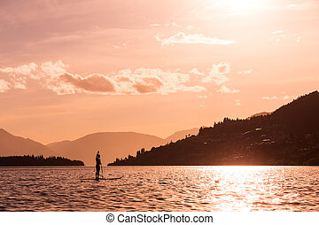 young female paddles a paddleboard off Lake Wakatipu at the...