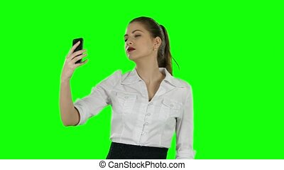 Businesswoman photographs with phone. Green screen