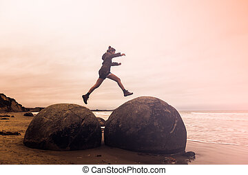 young adult woman jumping on Moeraki Boulders, South Island New Zealand