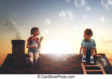 child blowing soap bubbles - happy childhood! boy and girl...