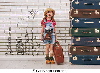 Dreams of travel - happy child girl against a white brick...