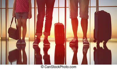 family at airport - Happy family with suitcases in the...