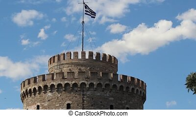White Tower in Thessaloniki, Greece. Greek flag waving on...