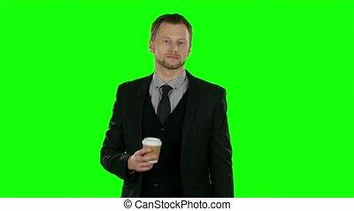 Businessman walking and drink coffee. Green screen -...