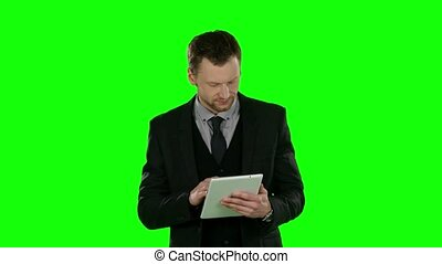 Businessman watching something in laptop and angry. Green...