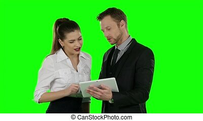 Two office worker look at a laptop together. Online shopping, Green screen