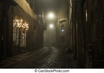 Old European narrow empty street of medieval town on a foggy...