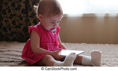 Small baby lying on sofa and playing with tablet