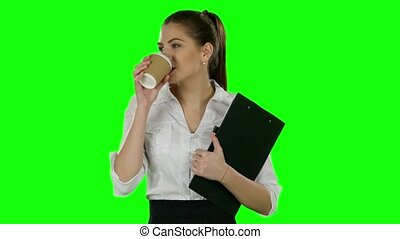 Business woman drink coffee with folder in hands. Green...