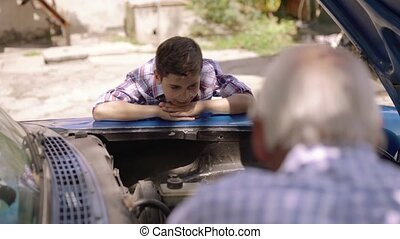 Boy With Grandpa Learning Car Engines From Senior Man -...