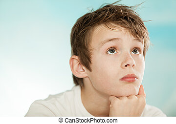 Handsome young teenage boy lost in thought