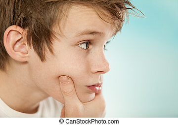 Thoughtful young boy grasping his chin - Close up on the...