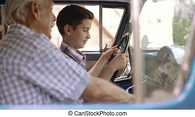 Portrait Grandpa Giving Driving Lesson To Boy In Old Car -...