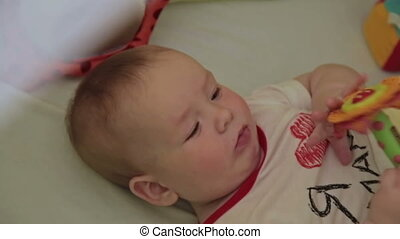 Baby lies with toy - Baby lies on back with toy in bed and...