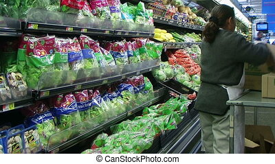 Woman Stocking Lettuce In Produce